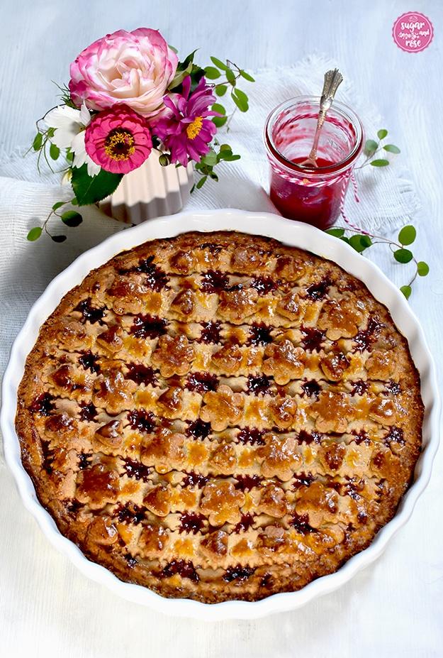 Frisch gebackene Linzer Torte in runder weißer Keramikform, ungezuckert, dahinter eine kleine Vase mit rosa Blüten und grünen Blättern, daneben ein Glas Himbeergelee mit Silberlöffel