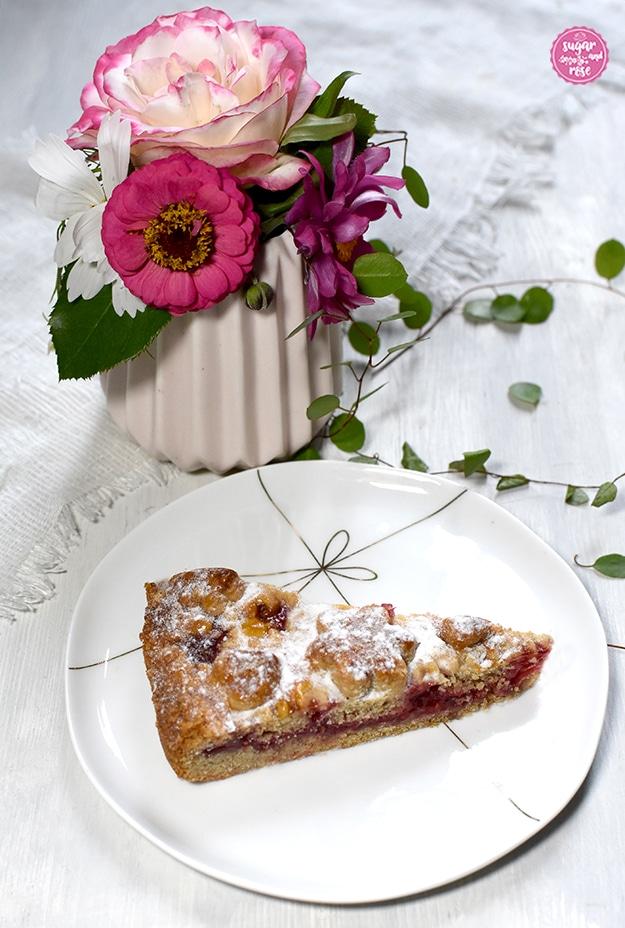 Ein Stück der Linzer Torte auf einem weißen Keramikdessertteller mit zarter goldener Masche als Dekor, im Hintergrund eine dezent rosa Vase mit Rose, Zinnie und weißen und lila Cosmeablüten, davor kleine grüne Blätter liegend