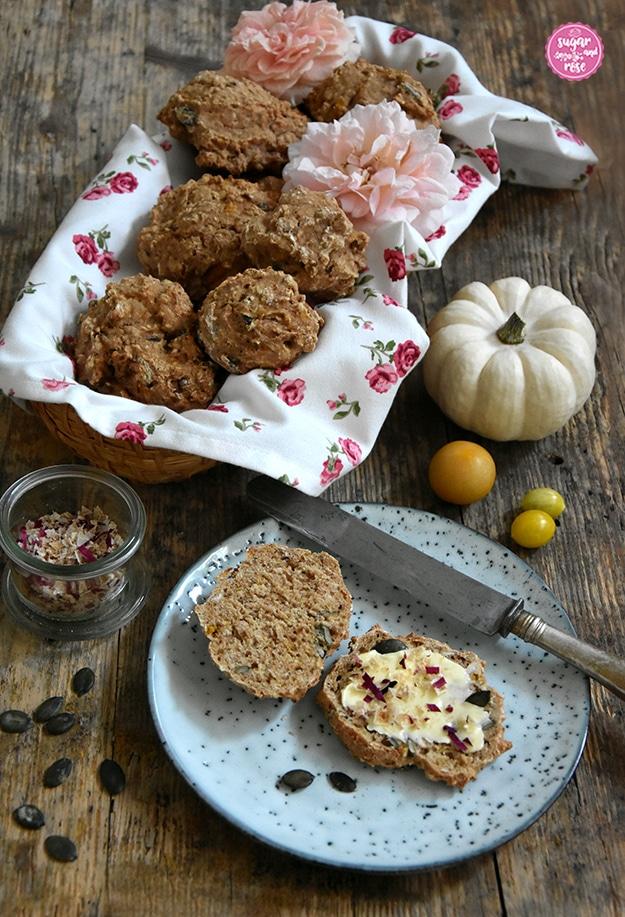 Mehrere Vollkornweckerl in einem Brotkörbchen mit Geschirrtuch mit kleine Rosenblüten, davor ein grauer Keramikteller mit einem aufgeschnittenen Brötchen, bestrichen mit Butter, bestreut mit Kürbiskernen, grobem Rosensalz, daneben ein altes Messer und kleine gelbe Tomaten