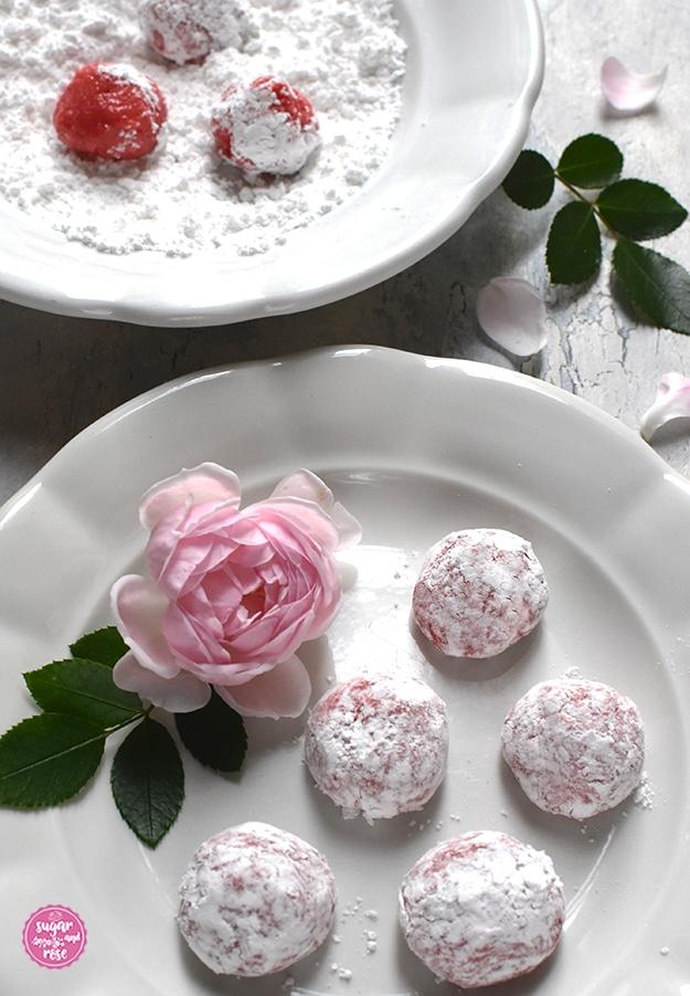 Großaufnahme von den Cookieteigkugeln mit Puderzucker, am Teller ein hellrosa Rosenblüte und ein grünes Rosenblatt