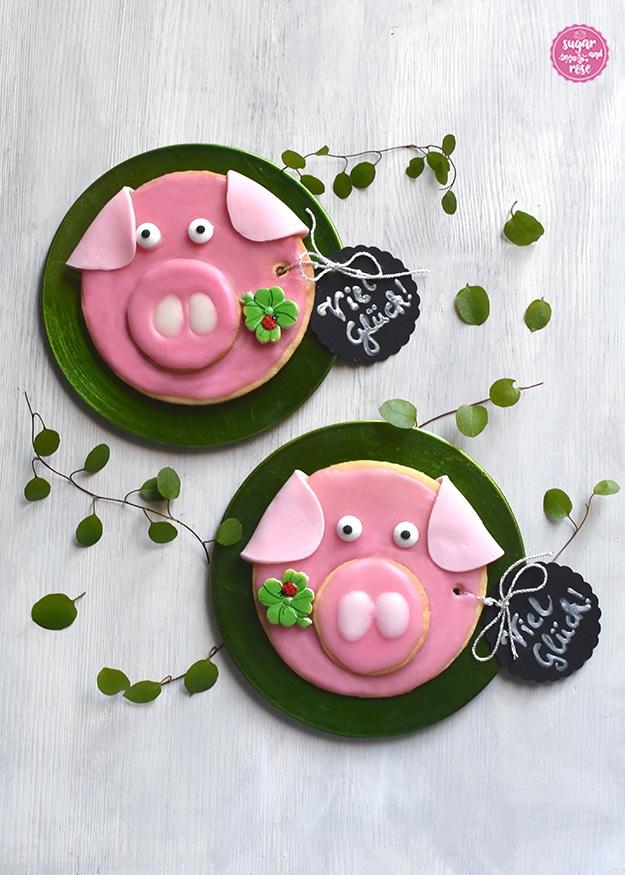 """Zwei runde Glücksschweinchen-Kekse mit rosa Glasur und einem Kleeblatt im Rüssel mit jeweils einem schwarzen Kartonanhänger mit """"Viel Glück"""" in Silberschrift, auf jeweils einem kleinen grünen runden Tellerchen liegend, rundum grüne Blätter"""