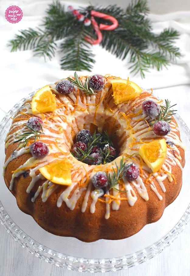 Orangen-Cranberry-Kranz auf gläserner Etagere mit gezuckerten Cranberrys in der Mitte und als Deko, dahinter Tannenzweige und rote Zuckerstangen