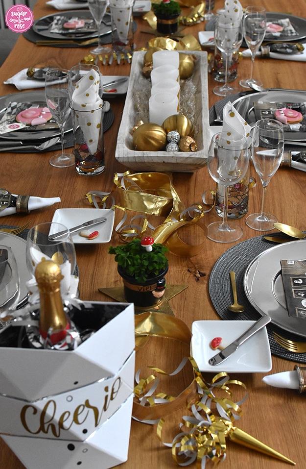 """Tischdeko mit Glücksklee und Sektflasche in einem weißen Kühler mit der Aufschrift """"Cheerio""""."""