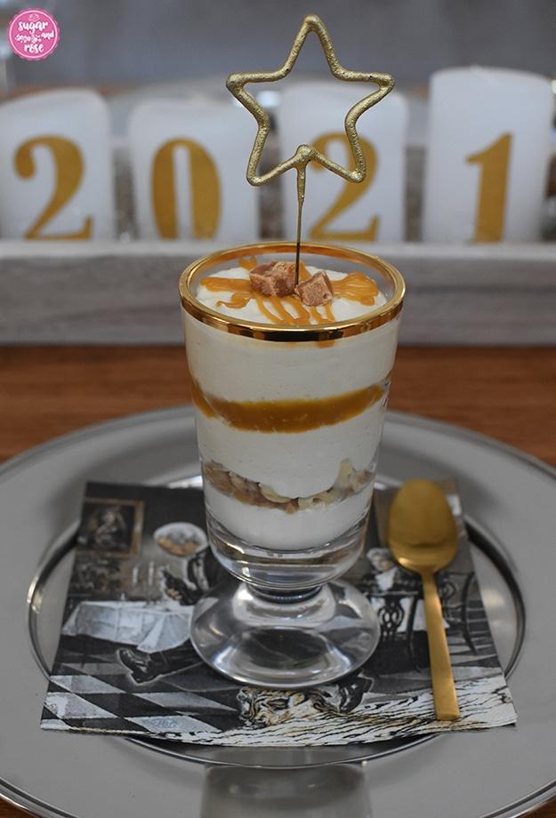 """Ein Glas mit Karamell-Mousse im Teeglas mit Sternspritzer auf einem silbernen Platzteller mit einer schwarz-grauen Serviette mit dem Motiv """"Dinner for one"""", daneben ein goldener Teelöffel, im Hintergrund vier weiße Kerzen mit der Aufschrift 2021"""