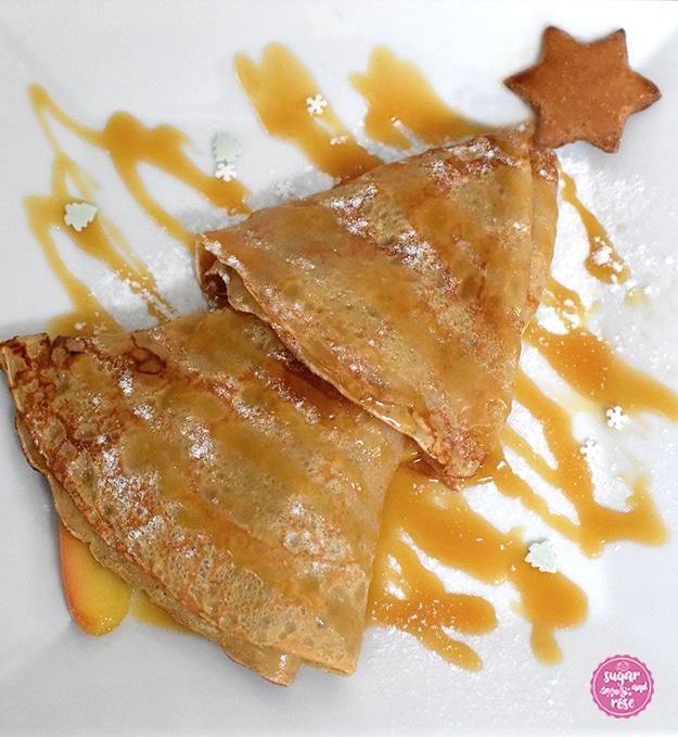 Zwei Lebkuchen-Creps zusammengeklappt und in Form eines Tannenbaums ineinander gesteckt, an der Spitze ein kleiner Lebkuchenstern, streifenförmig übergossen mit Karamellsauce