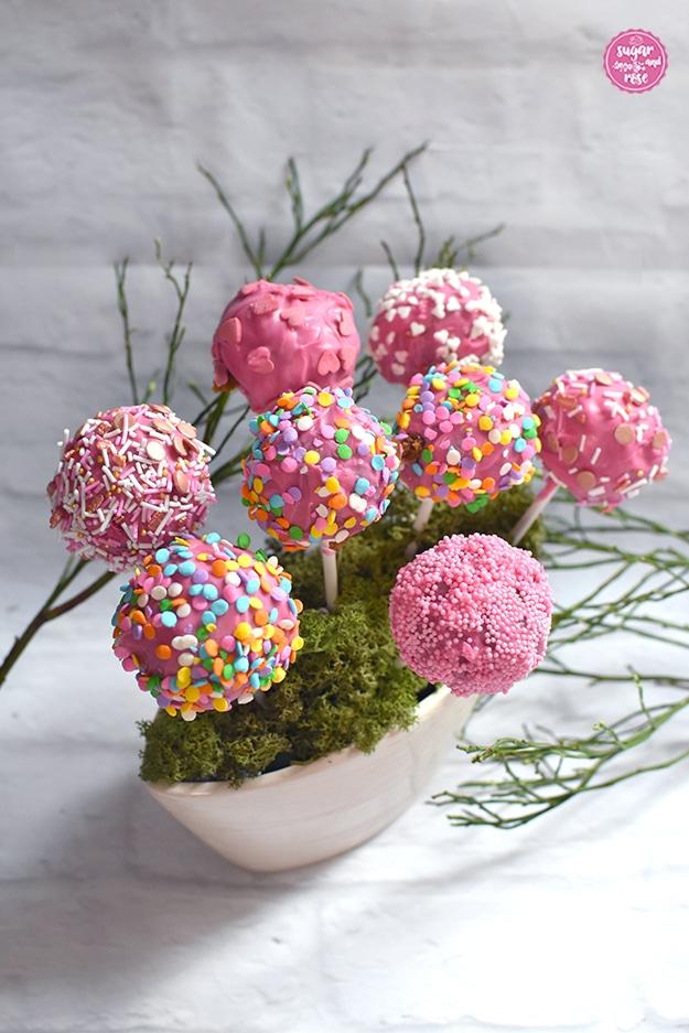 Acht kugelförmige rosa Cak-Pops eingesteckt in eine moosbedeckte cremefarbene, mandelförmige Keramikblumenschale, dahinter grüne Heidelbeerzweige