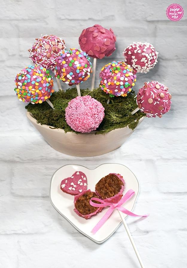 Acht rosa Cake-Pops in moosbedeckter Keramikschale, davor ein kleiner herzförmiger Keramikteller in weiß mit zartem grauem Rand, darauf ein halbierter Cake-Pop mit rosa Schleife. Die braune Punschfüllung ist sichtbar