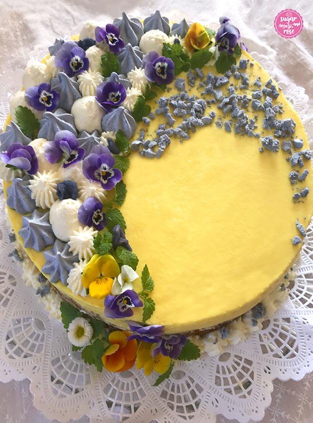 Satt gelbe Eierlikör-Torte von oben, zur Hälfte dekoriert mit leuchtend violetten Stiefmütterchen, blassvioletten Baisertuffs, weißen Cremetupfen und einigen zerbröselten Baiserstücken.