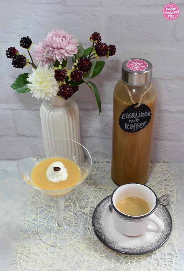 Kaffee-Eierlikör abgefüllt in Glasflasche mit schwarzen Etikett, davor ein Cocktailglas mit Kaffee-Eierlikör, daneben eine Porzeallanvase mit rosa und weißen Kunstblüten, im Vordergrund eine grau-weiße Moccatasse mit einem Espresso