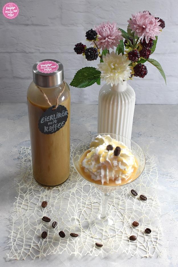 Kaffee-Eierlikör abgefüllt in Glasflasche, davor ein Cocktailglas mit Kaffee-Eierlikör und einer großen Sahnehaube, daneben eine weiße kleine Porzeallanvase in Flaschenform mit rosa und weißen Kunstblüten sowie Brombeeren