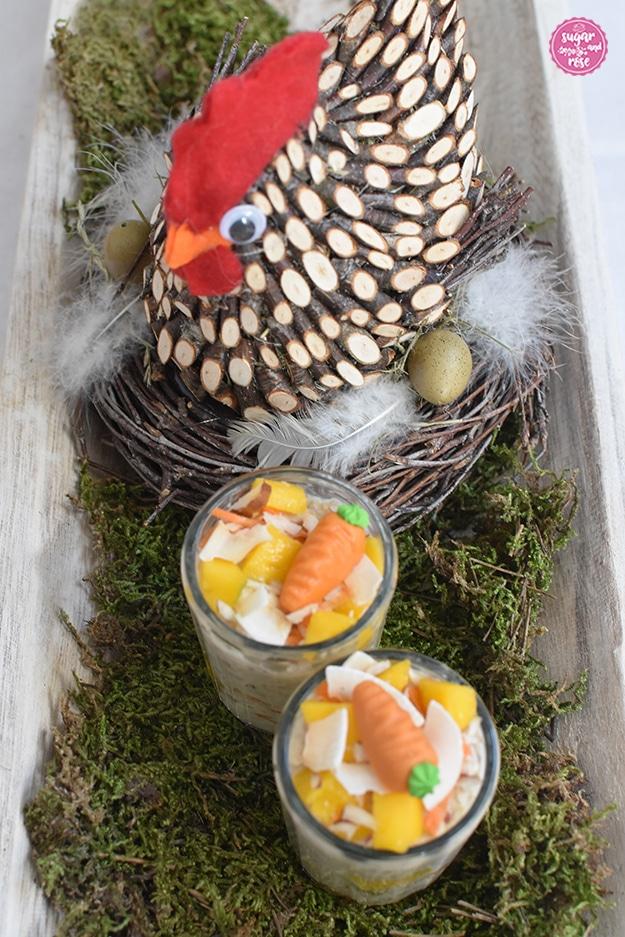 Zwei Gläser mit Overnight Oats mit Mango und Karottendeko im Vordergrund auf grünem Moos, dahinter eine Henne aus kleinen Holzstückchen mit rotem Filzkamm