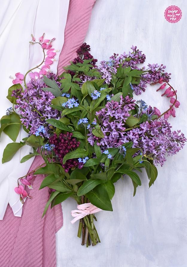 Muttertagsblumenstrauß aus Flieder, Vergissmeinnicht und Herzblumen mit einem hellrosa Bändchen zusammengebunden, auf einem weißen Untergrund mit rosa Tuch liegend.
