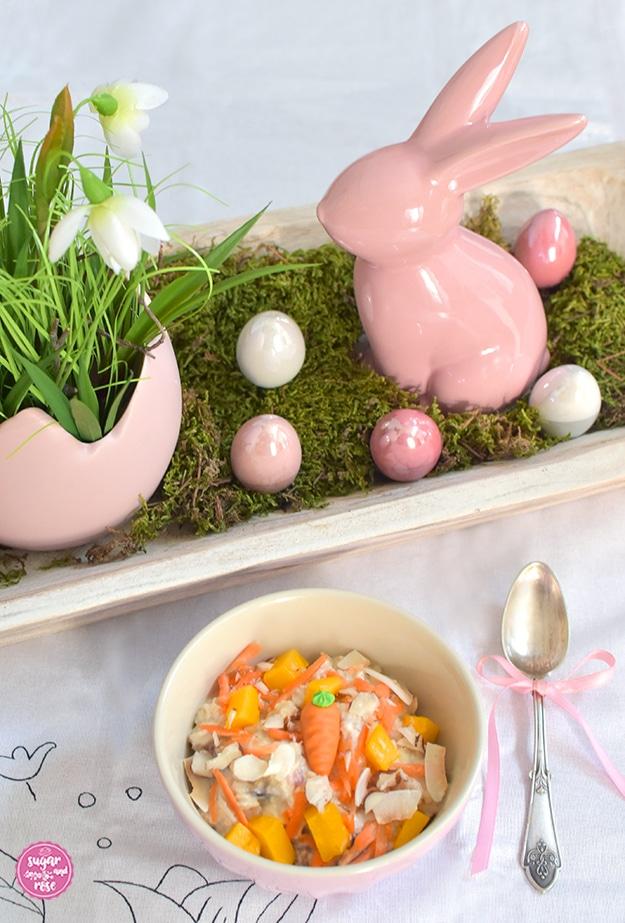 Rosa Keramikschälchen mit Overnight Oats und Karotten und Mango, daneben ein Siberlöffelchen mit rosa schleife, dahinter eine weiße Holzschale mit rosa Porzellanhase, perlmuttschimmernde rosa Porzellaneier und eine rosa Blumenschale in Form eines zerbrochenen rosa Eis