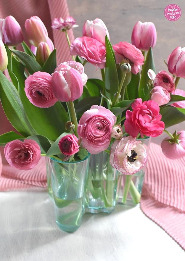 Eine mittelgroße durchsichtige grüne Aalto-Vase im klassischen skandinavischen Design mit einem dichten Strauß an rosa-weißen Tulpen und Ranunkeln in verschiedenen Rosatönen, im Hintergrund ein pastellrosa Tuch mit Faltenwurf.