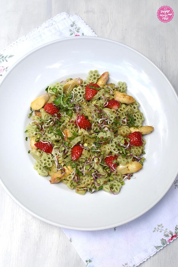 Tiefer weißer Pastateller mit hellgrünen Blütennudeln mit gebratenem weißem Spargel und Erdbeeren