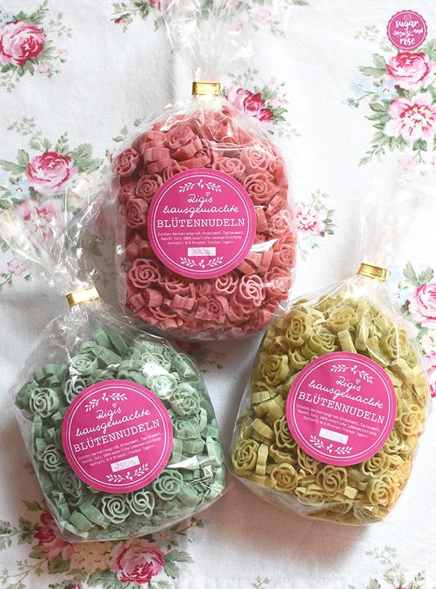 Drei Packungen Blütennudeln: rosafarbene, hellgrüne und mintgrüne Rosennudeln in Cellophanpackungen mit rosa Aufkleber