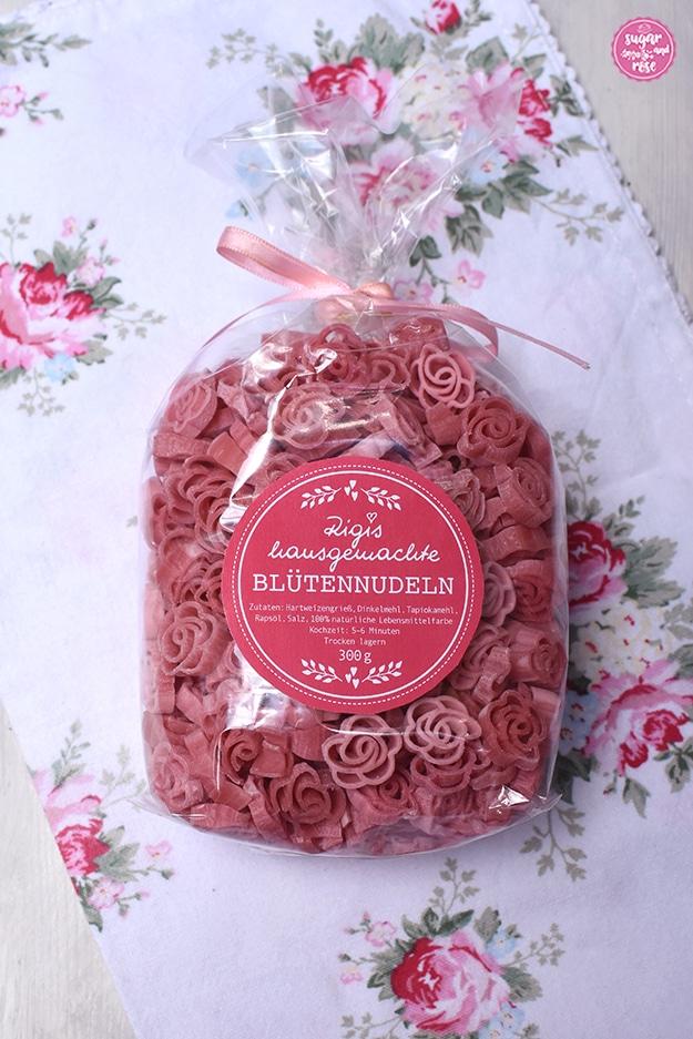 """Eine Cellophanpackung Rigis Blütennudeln in Rosenform mit rundem rosafarbenen Aufkleber """"Rigis hausgemachte Blütennudeln"""" und rosa Schleife auf Geschirrtuch mit rosa Röschen"""