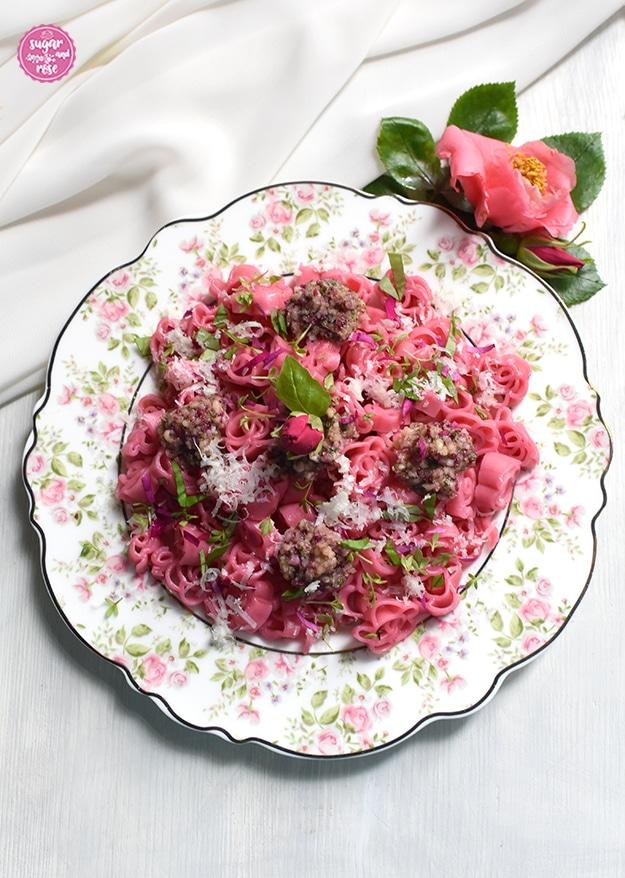 Rosafarbene Blütennudeln mit Rosenpesto auf einem Teller mit Rosendekor, daneben eine lachsfarben Kamelienblüte