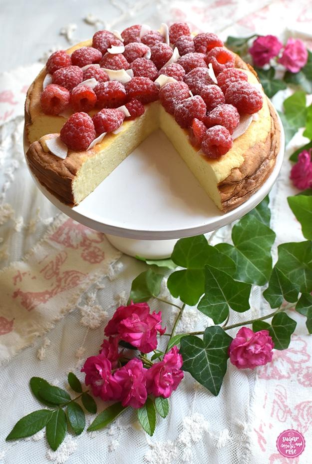 Topfenkuchen mit Himbeeren und Kokoschips auf weißer Etagere, ein Viertel des Kuchens ist herausgeschnitten, der saftige Topfenkuchen sichtbar