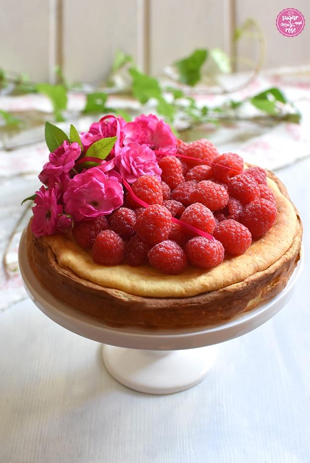 Topfen-Kokos-Kuchen mit Himbeeren  und pinkfarbenen Rosenblüten sowie einer rosa Schleife auf weißer Etagere