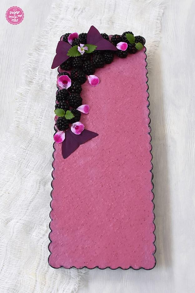Ombré-Brombeertarte in dunkler Tarteform auf weißem Tuch, dekoriert mit Brommberen, rosa Geranienblüten und rotem Sauerklee