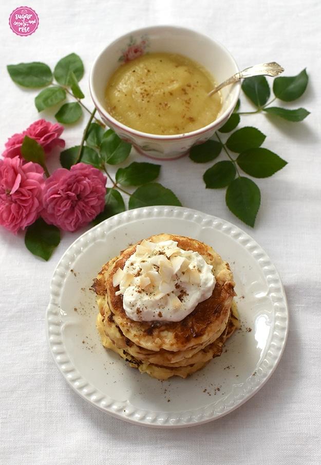 Pancakes gestapelt auf weißem Desserteller, dahinter eine Blütenschale mit Apfelmus und rosa Röschen als Deko