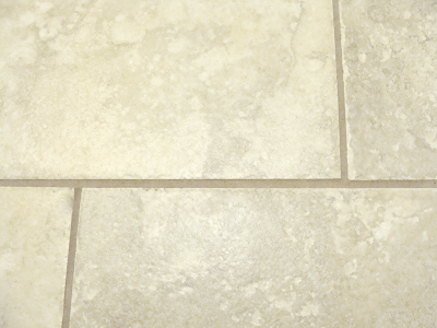 close up of dirty grout on laundry room tile floor before