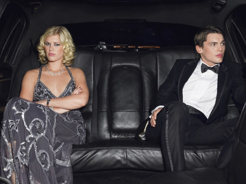 Bored young couple in limousine after breaking up
