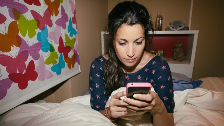 girl in her bedroom texting