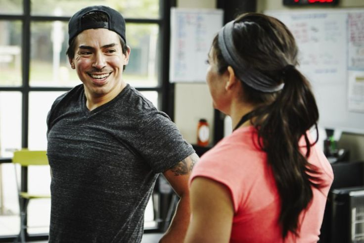 man making small talk to a woman in the gym