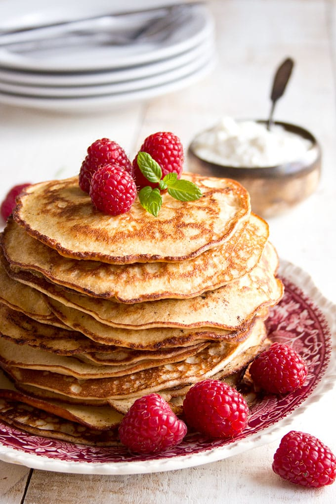 Stack of almond cream cheese pancakes strewn with raspberries with a bowl of yoghurt in the background