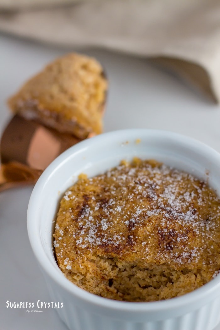 snickerdoodle keto mug cake with spoonful removed and left laying beside mug