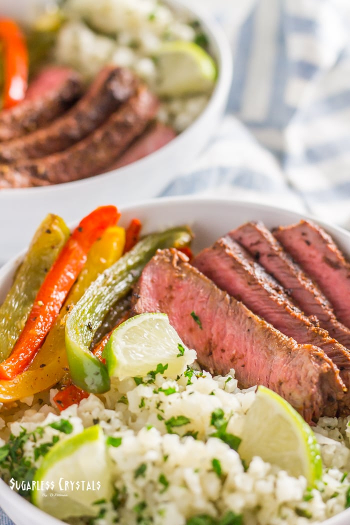 healthy steak fajitas bowl with cilantro lime cauliflower rice and bell peppers