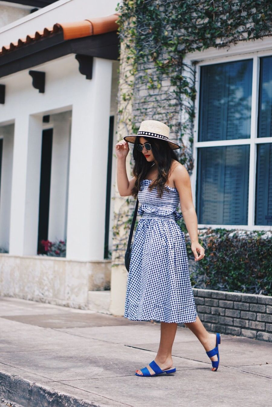 Fashion blogger styles gingham skirt outfit with sandals and hat