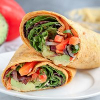 Hummus veggie wraps. Sauted vegetables, avocado, hummus, greens and feta cheese rolled into a sun-dried tomato wrap. Light, flavorful and perfect for a summer lunch.