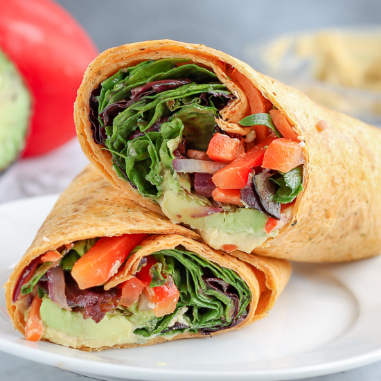 Hummus veggie wraps. Sauted vegetables, avocado, hummus, greens and feta cheese rolled into a sun-dried tomato lunch. Light, flavorful and perfect for a summer lunch.