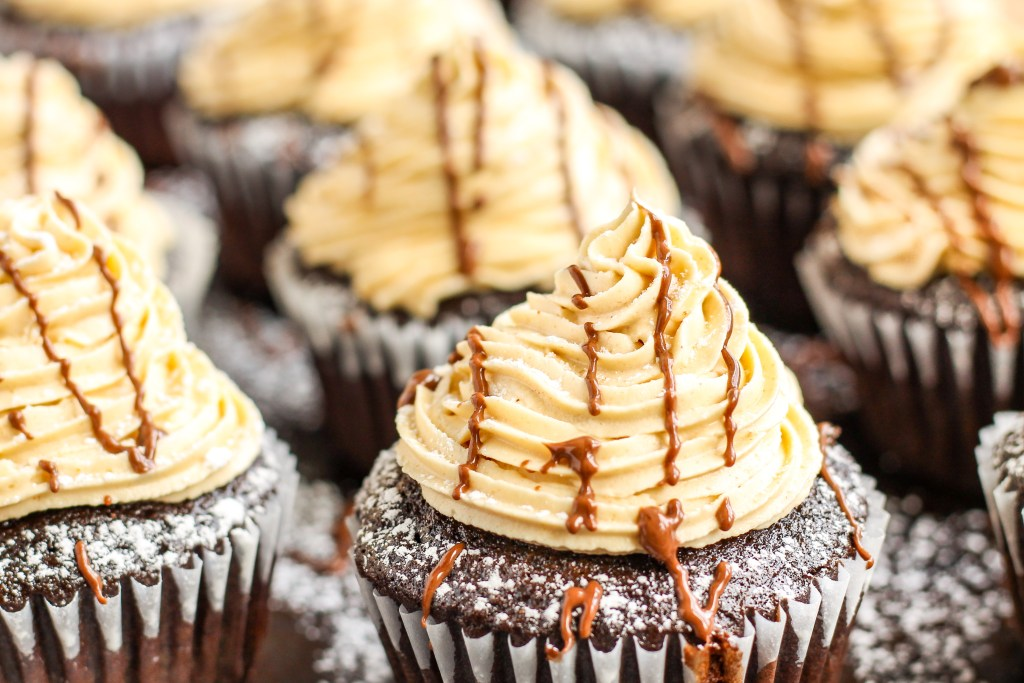 Muddy Buddy Cupcakes. Chocolate cupcakes filled with homemade buddies, topped with peanut butter buttercream, and finished with powdered sugar and chocolate ganache.