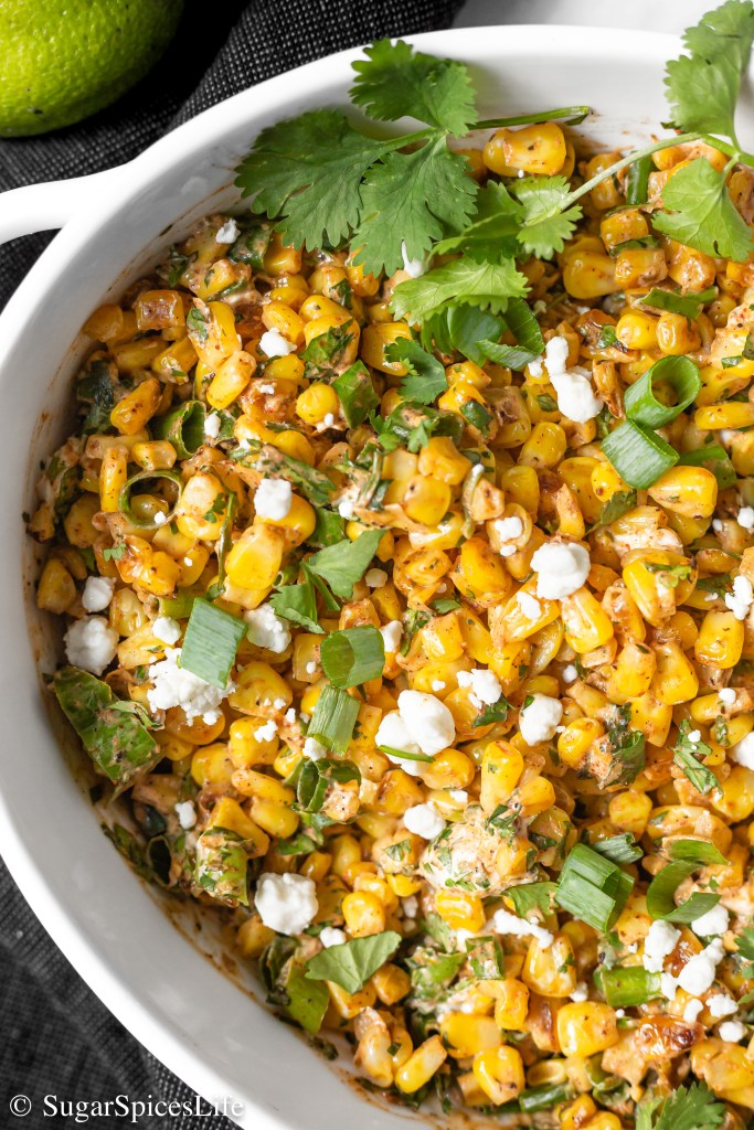 Corn roasted in a skillet, tossed in a creamy, spicy lime sauce, and topped with goat cheese and onions. This Skillet Mexican Street Corn is the best way ever to eat corn.