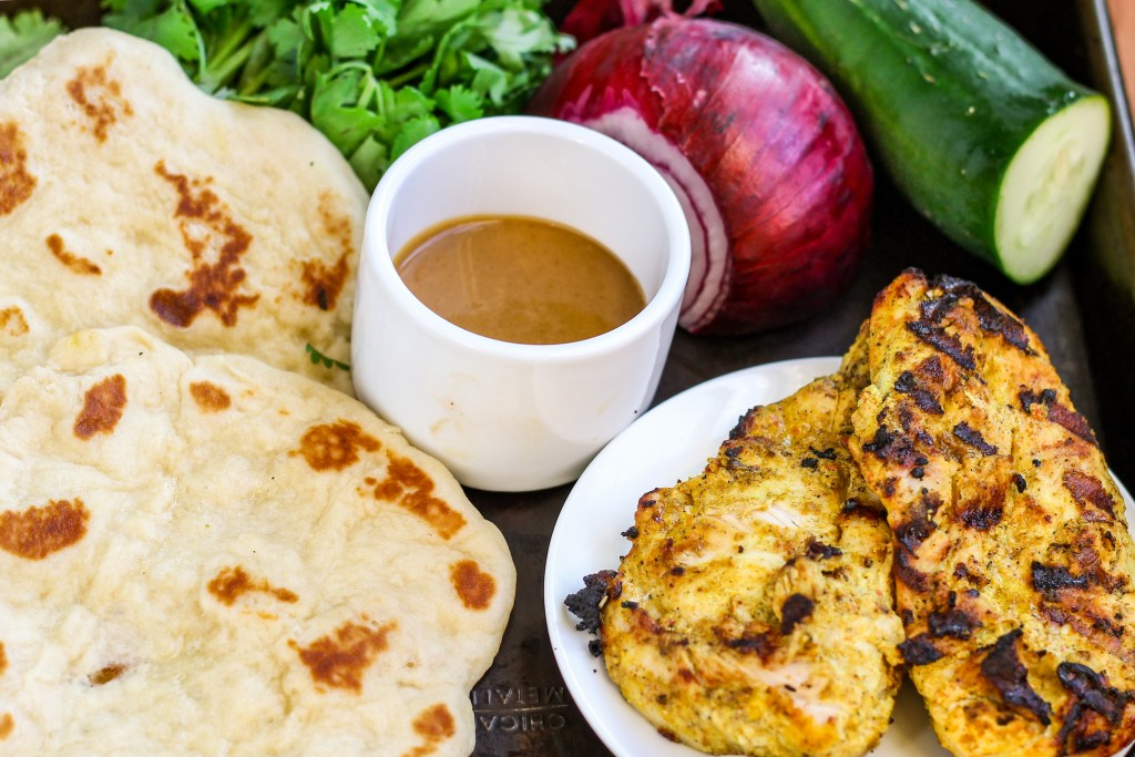 Tandoori Chicken with Peanut Sauce. Chicken marinated in tandoori style spices, then grilled and topped with a savory peanut butter coconut milk sauce. Full of delicious flavors!