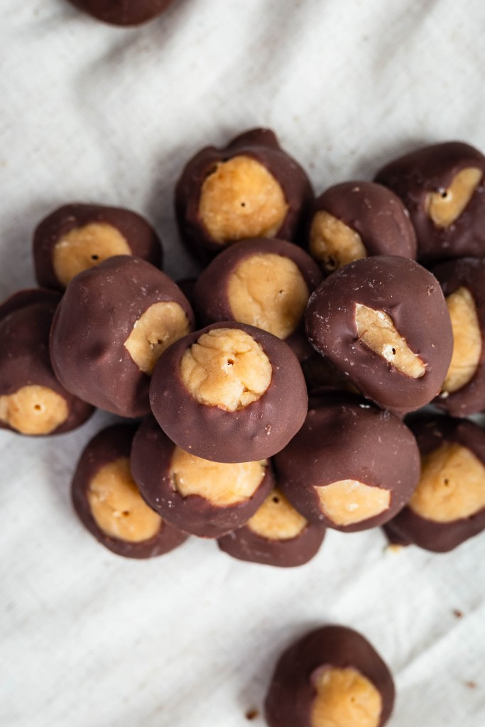 Buckeyes (Peanut Butter Chocolate Candy). Honey nut peanut butter balls dipped in semi-sweet chocolate. A delicious candy for any time of the year!