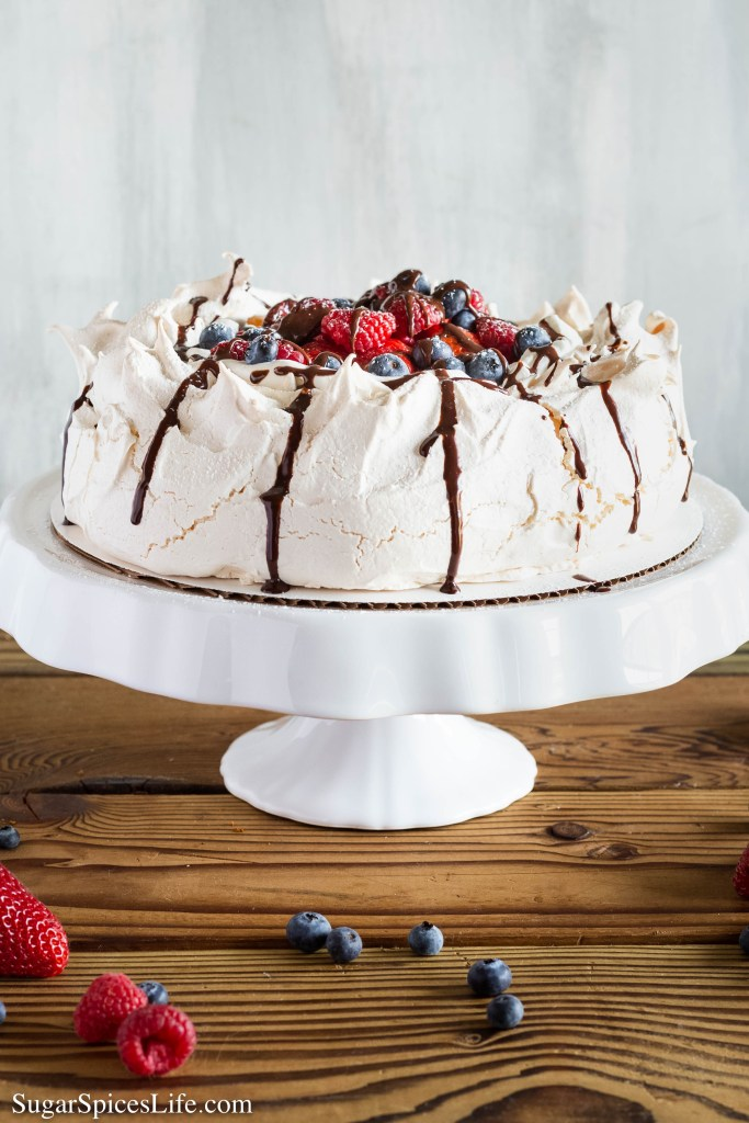 Pavlova with Fresh Whipped Cream. Light, airy pavlova filled with fresh whipped cream and berries. Drizzled with chocolate ganache. An elegant, beautiful, delicious dessert!