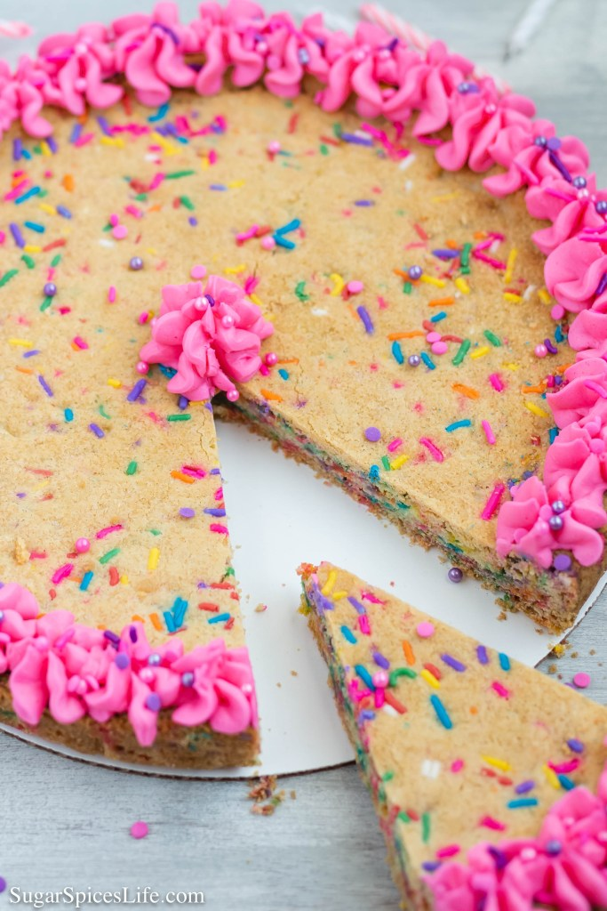 This homemade Funfetti Cookie Cake is a soft, sugar cookie filled with lots of sprinkles and topped with buttercream frosting. Delicious and perfect for any celebration!