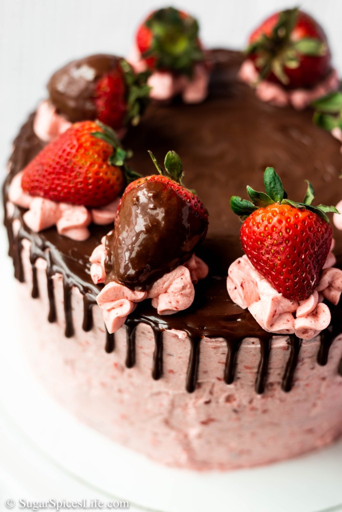 This Chocolate Covered Strawberry Cake has soft, chocolate cake layers filled with a strawberry chocolate ganache, frosted with strawberry buttercream, and finished with chocolate ganache and chocolate covered strawberries. A chocolate covered strawberry turned into a cake!