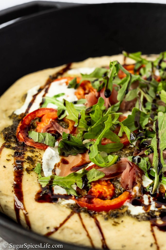 This Prosciutto Caprese Skillet Pizza has a fluffy, homemade yeast crust that is topped with pesto, fresh mozzarella, prosciutto, greens, and a balsamic reduction. It's quick and easy, healthier than take out, and delicious!