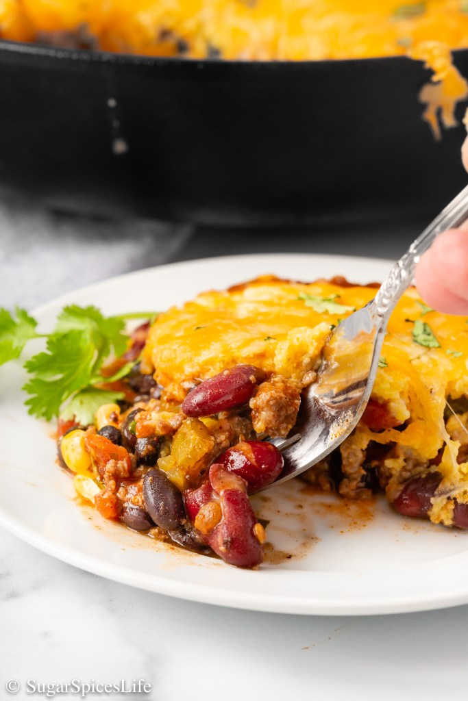 Ground beef, beans and vegetables cooked in a well seasoned sauce, then topped with cornbread and cheese. This Skillet Beef and Cornbread Casserole is a hearty meal that comes together quickly!