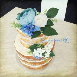 Naked vanilla and lemon cake with artificial flowers