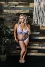 Anniversary Boudoir Sugashoc Photography standing in front of pallet wall wearing light blue bra and panty