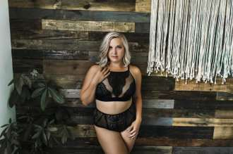 Anniversary Boudoir Sugashoc Photography standing against pallet wall wearing black lace top and panty