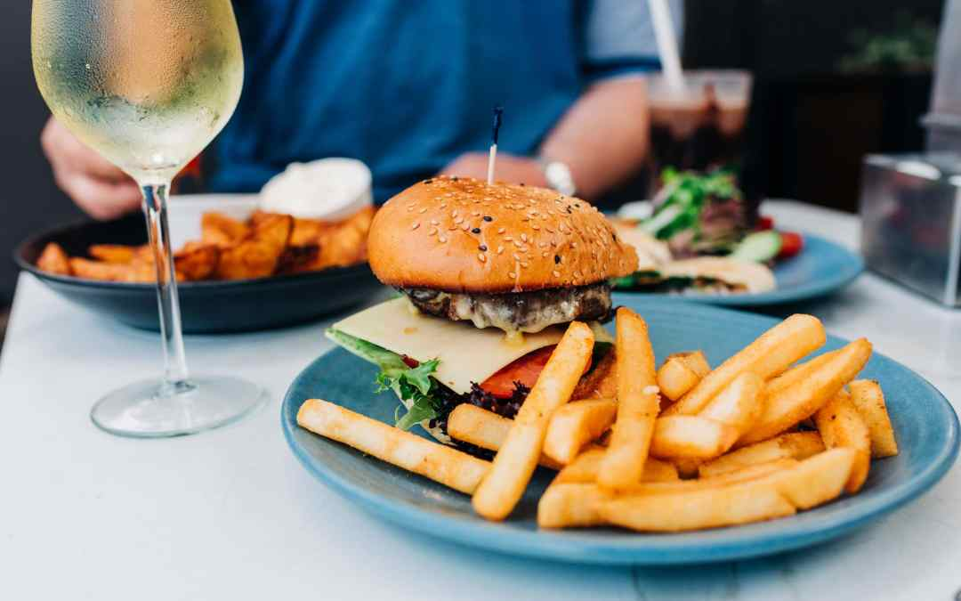 White wine in a large glass next to a hamburger and fries | How to wind down after a busy week - Suger Coat It