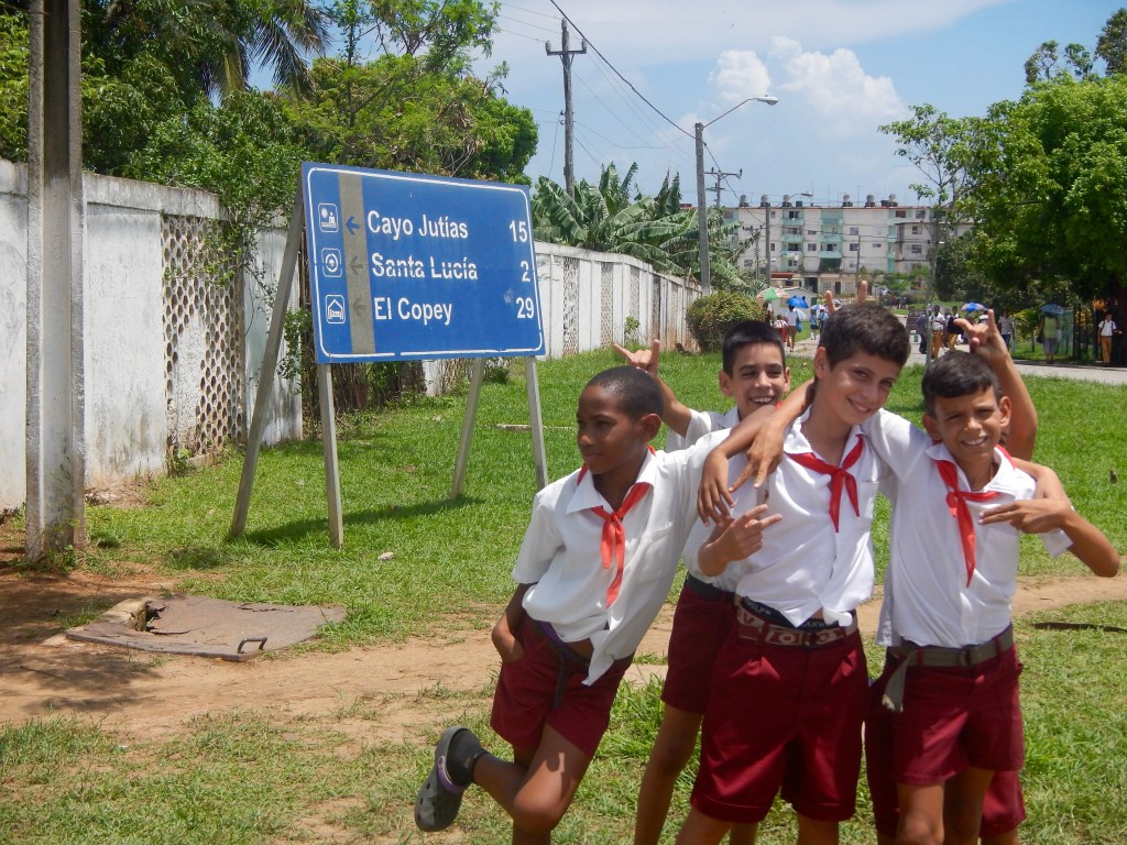 School kids in front of a street sign to Cayo Jutias, Cuba.